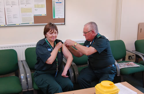 Dennis Clarke giving the flu vaccination to a member of staff