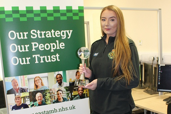 Woman holding an award in front of a stand up banner.