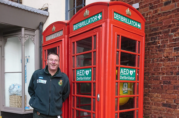 man stands next to red telephone box/defib